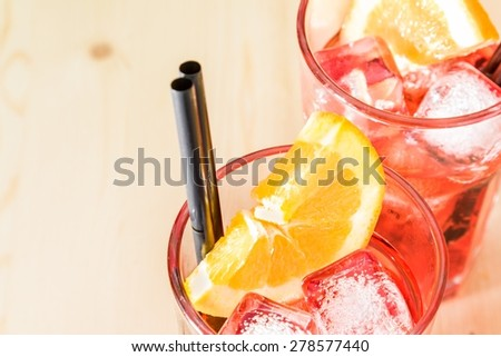 close-up of glass of spritz aperitif aperol cocktail with orange slices and ice cubes on wood table with space for text