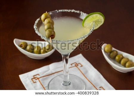Close up of glass with margarita cocktail garnished with salt rim, lime and olives on a table. - stock photo