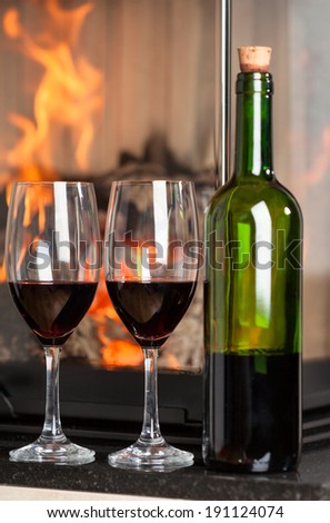 Close up of glasses and delicious red wine standing near to fireplace - stock photo