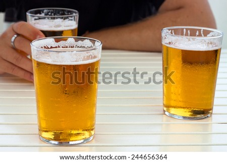 Close up of glasses of fresh beer and hands on table. - stock photo
