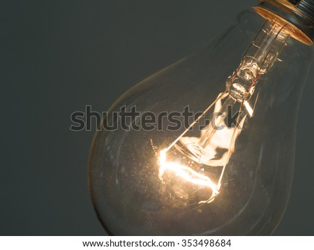 close up of glowing element in the incandescent light bulb, showing hot wire glow by electric current flowing in the tungsten filament - stock photo
