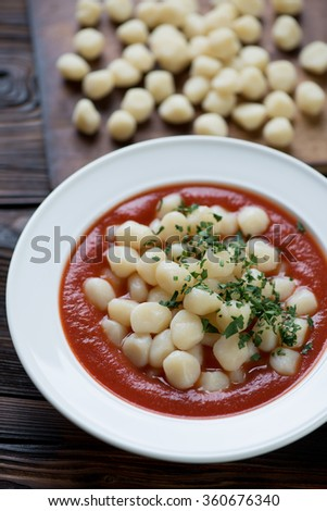Close-up of gnocchi with tomato sauce and fresh parsley - stock photo