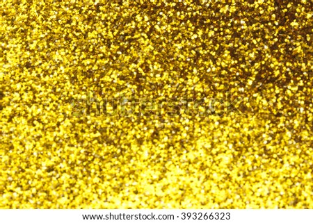 Close up of gold glitter shining in the light. Shollow depth of field.
