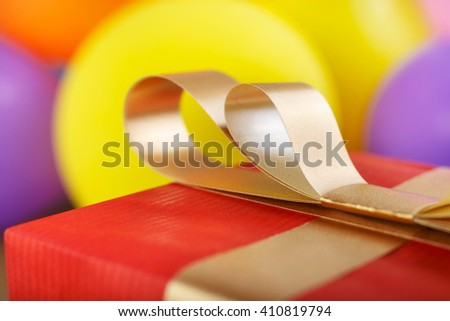 close up of golden bow red gift box with gold ribbon against the backdrop of colorful balloons - stock photo