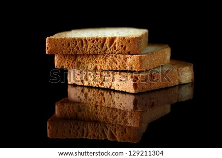 Close up of golden slices of toasts on black background with reflection