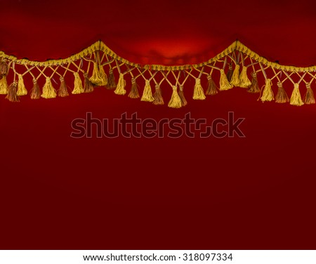 Close up of golden tassels hanging over red classic curtain. - stock photo