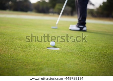 Close up of golf ball and a hole on a field - stock photo