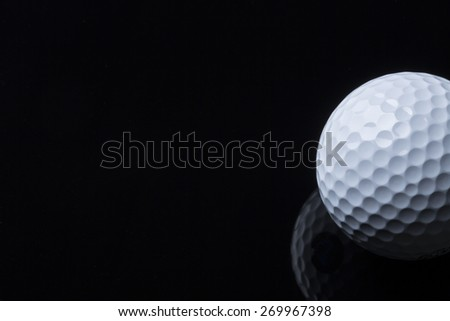 Close up of golf ball lying on black surface with reflection, isolated, copy space for text. - stock photo