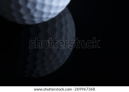 Close up of golf ball with reflection isolated on black background, copy space for text. - stock photo