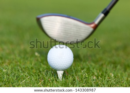 close-up of golf club with ball on tee