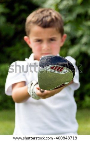 Close-up of golf driver club head held by little boy golfer - selective focus
