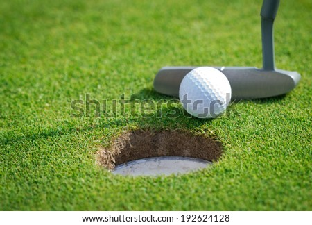 Close-up of golf hole with putter and ball  - stock photo