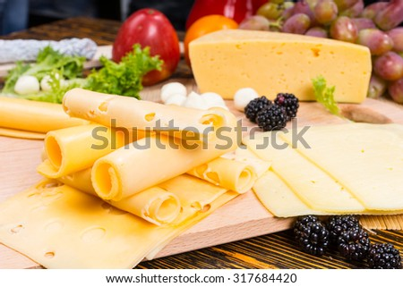 Close Up of Gourmet Cheese Board Appetizer Featuring Rolled Swiss Cheese Slices and Garnished with Fresh Fruit - stock photo