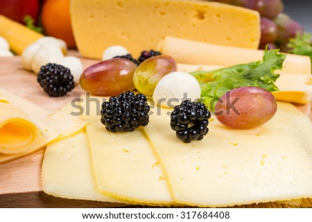 Close Up of Gourmet Cheese Board - Detail of Sliced Cheese Garnished with Fresh Fruit and Bocconcini - stock photo