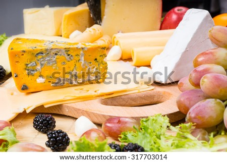 Close Up of Gourmet Cheese Board Featuring Bounty Different of Cheeses and Garnished with Fresh Fruit, Served on Wooden Cutting Board - stock photo