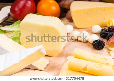 Close Up of Gourmet Cheese Board Featuring Variety of Cheeses and Garnished with Fresh Fruit - Detail of Appetizing Cheese Board - stock photo