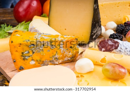 Close Up of Gourmet Cheese Board Featuring Variety of Cheeses, Cured Meats and Garnished with Fresh Fruit - stock photo