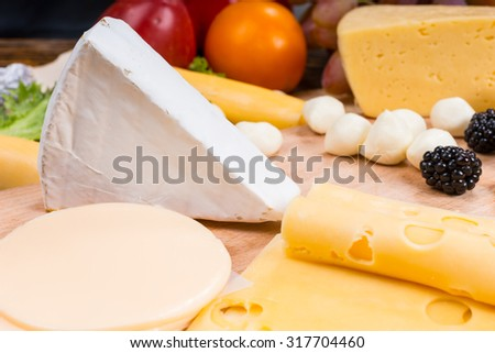 Close Up of Gourmet Cheese Board with Focus on Wedge of Brie Surrounded by Variety of Cheeses and Garnished with Fresh Fruit - stock photo