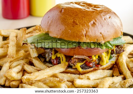 Close up of gourmet pub hamburger with bacon on black plate with french fries sitting on wooden table