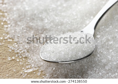 Close-up of granulated sugar in spoon and sugar pile. Shallow DOF. - stock photo