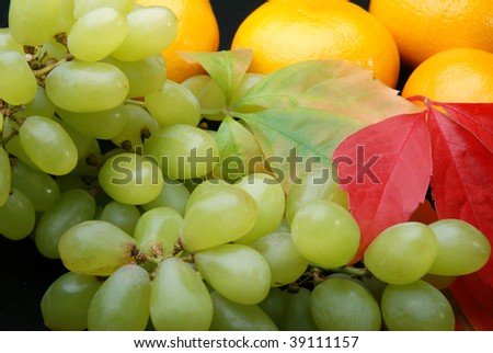 Close up of grapes and tangerine's on a black background