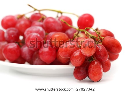 Close up of grapes on plate over white background.