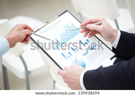 Close-up of graph and chart analyzed by businessmen - stock photo