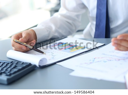 Close-up of graphs and charts analyzed by businessman  - stock photo