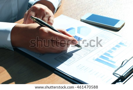 Close-up of graphs and charts analyzed by businesswoman