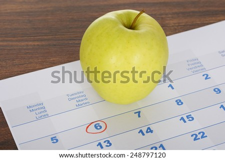 Close-up Of Green Apple On Calendar Marked With Red Marker - stock photo