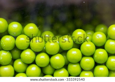 Close up of green candy gum balls in candy machine  - stock photo