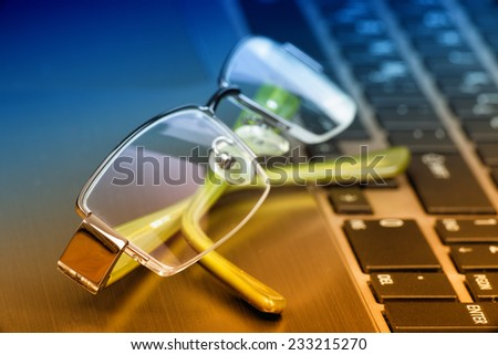 Close up of green eye glasses on open keypad of silver laptop