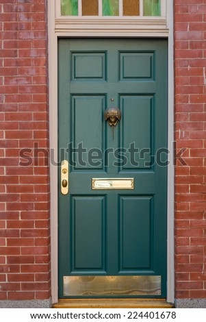 Close-up Of Green Front Door with Colorful Window Overhead in Brick Building - stock photo