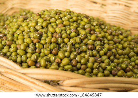 Close up of green mung beans in basket on wooden background
