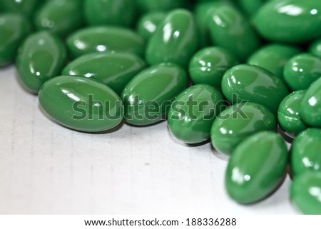 Close up of green pills on a white background