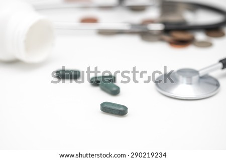 Close up of green pills or vitamin with stethoscope and coins on white for medical and health care background  - stock photo