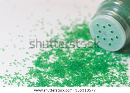 Close up of green sugar sprinkles on a gray background.