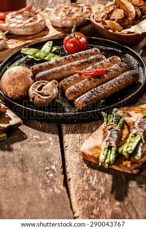 Close Up of Grilled Sausage and Vegetables on Rustic Wooden Table Surface with Foreground Copy Space