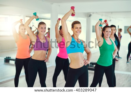 Close-up of group of young women doing exercise with dumbbells on triceps synchronously