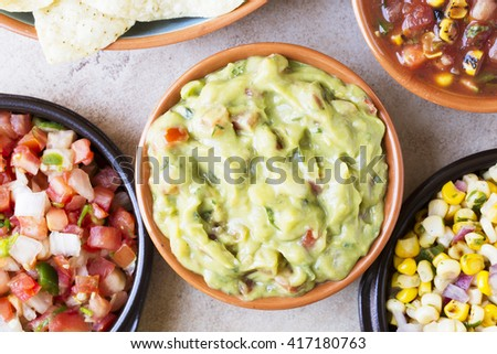 Close up of guacamole surrounded by pico de gallo and salsa, top down view