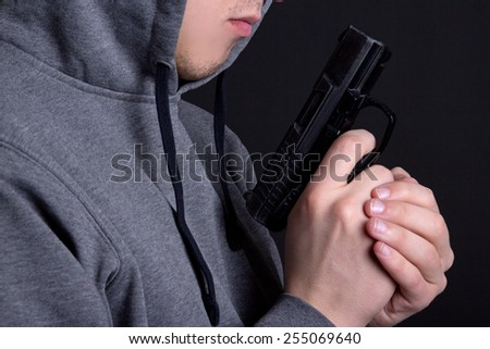 close up of gun in male hands over grey background