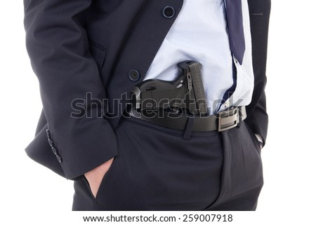 close up of gun in policeman or bodyguard pants isolated on white background - stock photo