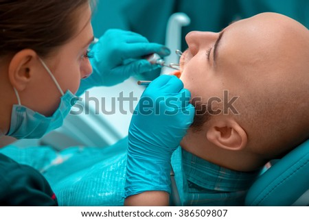 Close up of guy on the examination, the dentist checks the teeth. Medicine, dentist, health and stomatology concept