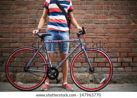 Close-up of guy with bicycle against brick wall - stock photo