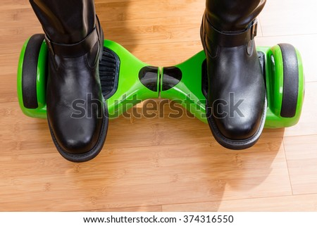 Close up of gyroscooter from front top view with riders feet over wooden floor - stock photo