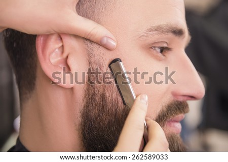 Close-up of hairdresser shaving an old-fashioned razor of satisfied client in professional hairdressing salon.