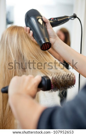 Close up of hairdressers hands drying long blond hair with blow dryer and round brush