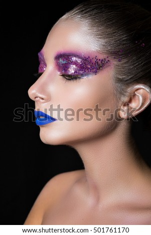 Close up of half-face woman with bright colorful make-up on black studio background