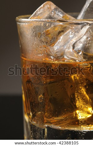 Close up of half of a Whiskey Glass with ice cubes and water droplets over a gradated background vertical composition