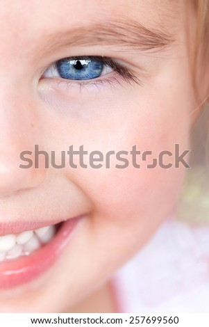 close up of half of girls face, smiling with beautiful blue eyes. - stock photo